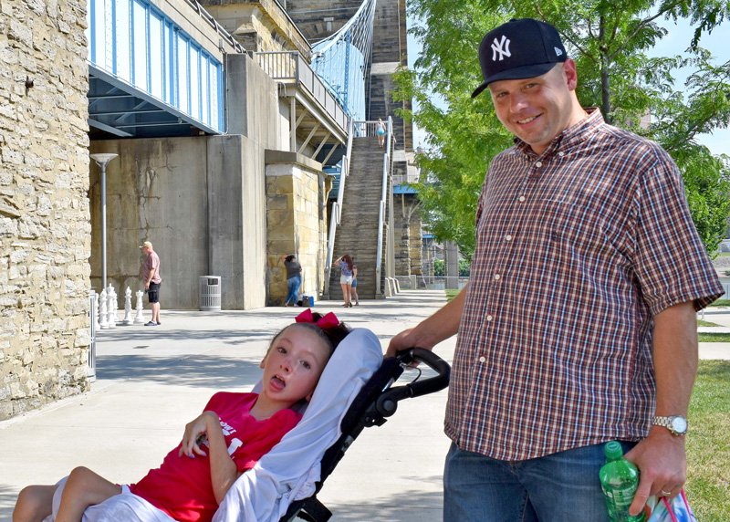 a father and daughter pose together under the Roebling suspension bridge