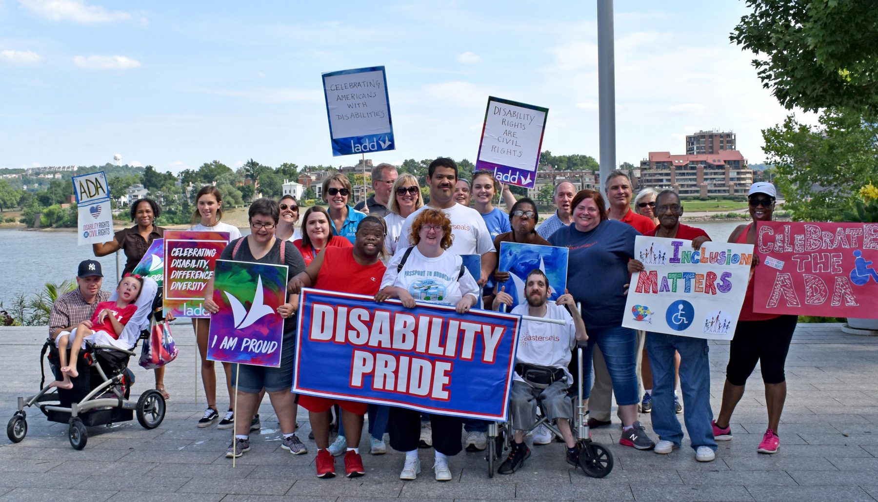 A large group of people pose with a sign that says disability pride during by the riverfront