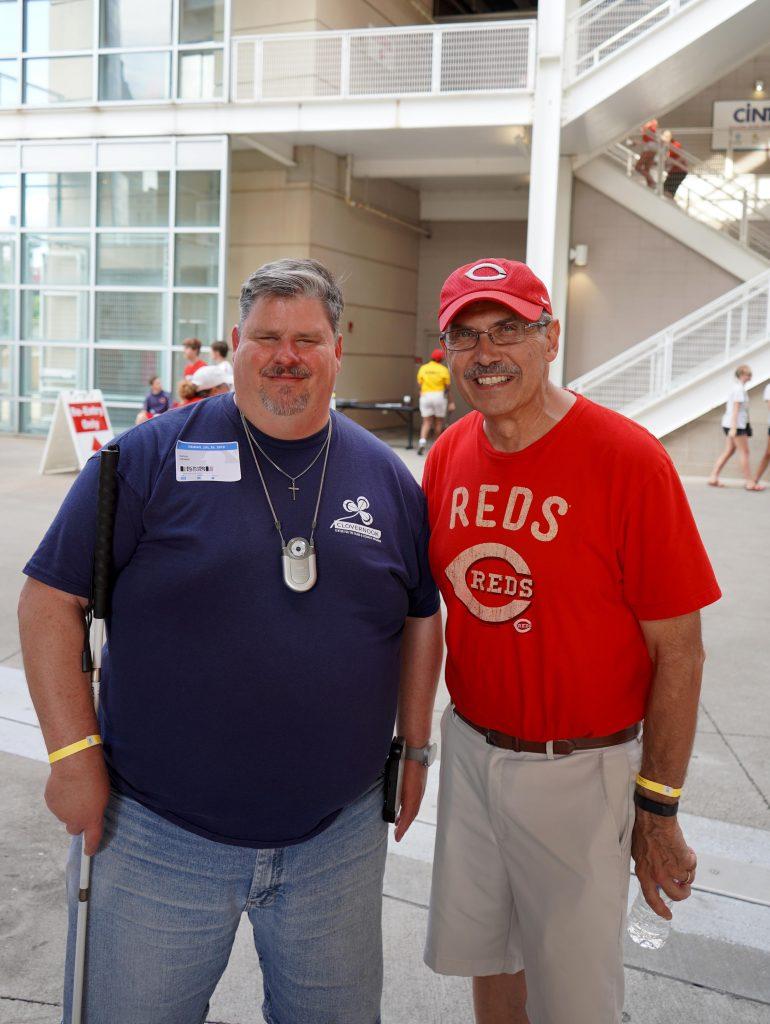 two men at a cincinnati reds game smiling