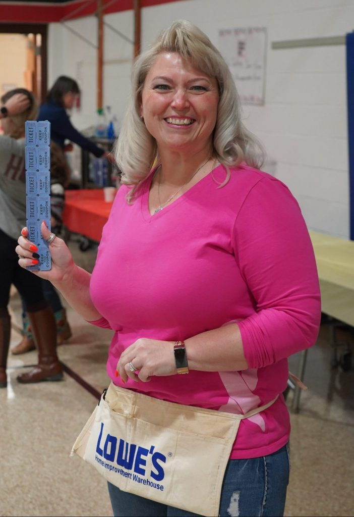 a woman smiles in a gym while holding raffle tickets