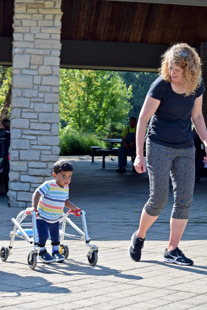 a young boy uses a gait trainer while a woman watches
