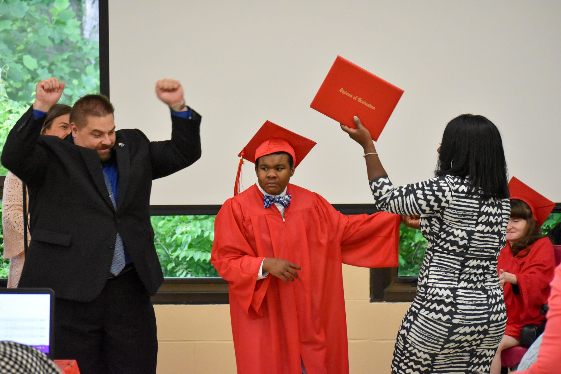 a young man in a red graduation gown and cap receives his diploma as people around him cheer