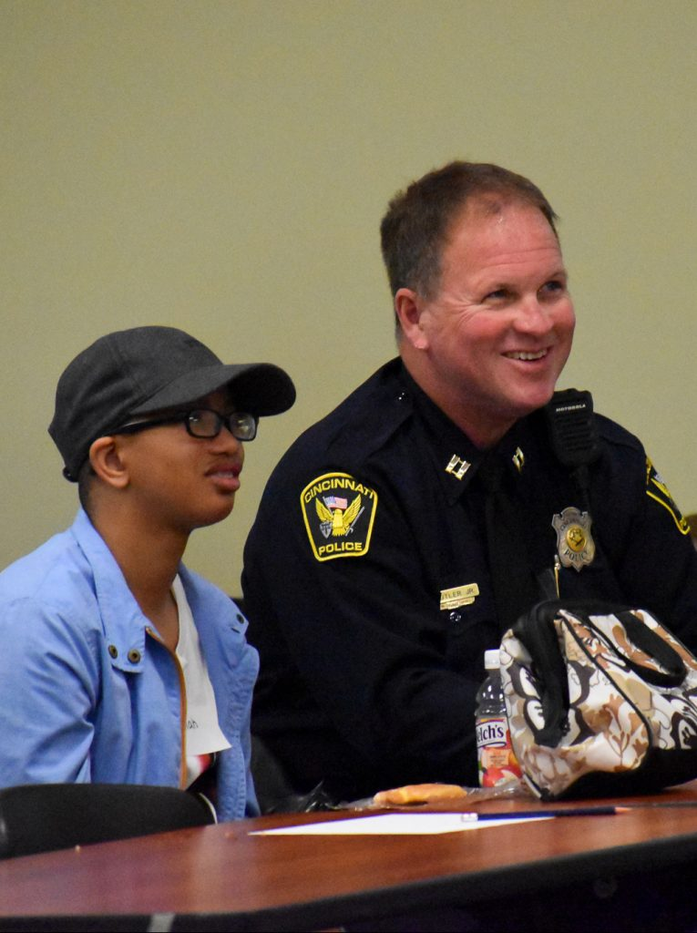 a young man and a police officer smiling