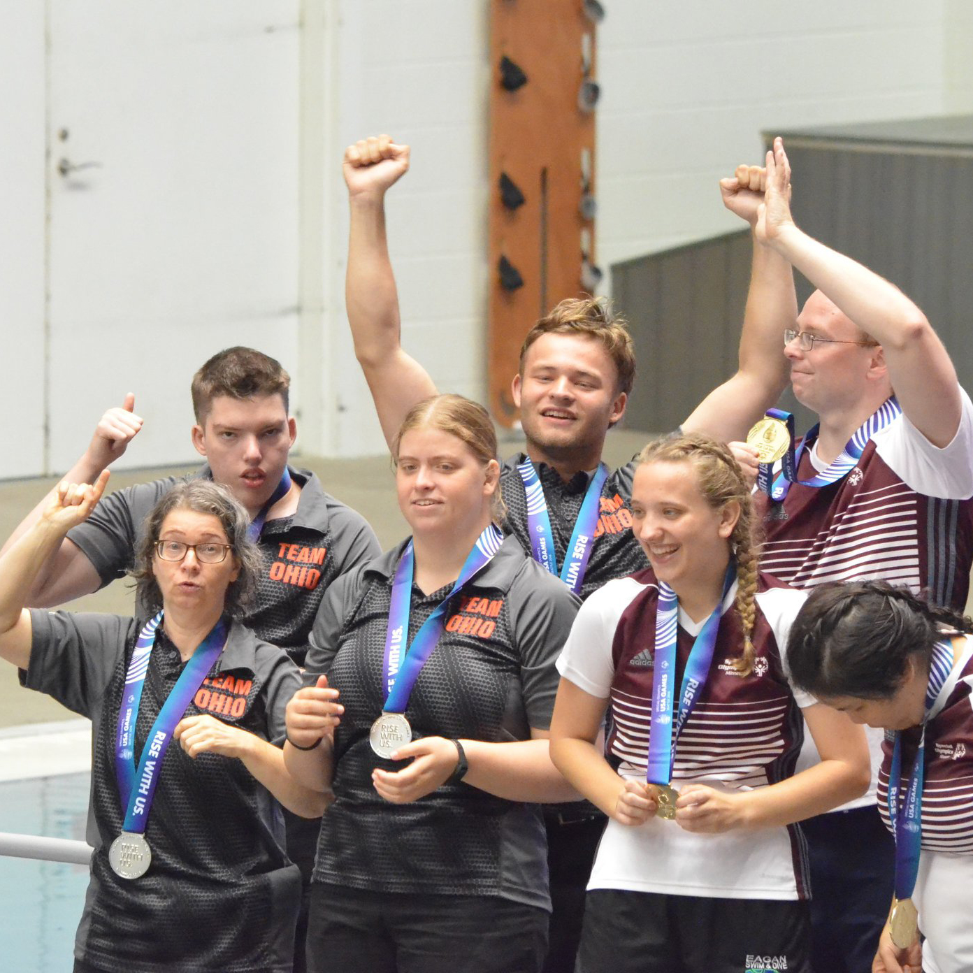 six young athletes wearing medals and cheering