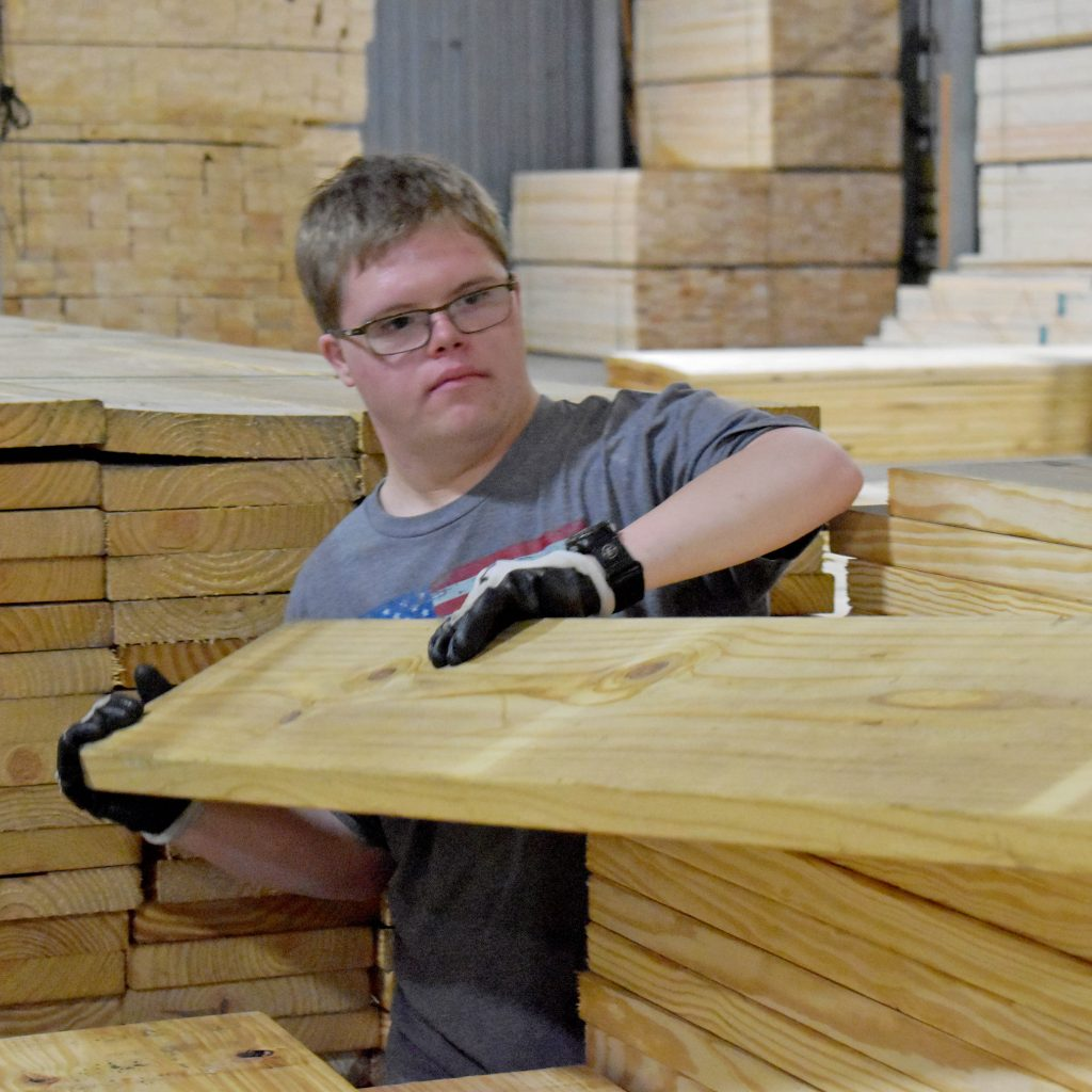 a man stacking lumber in a warehouse