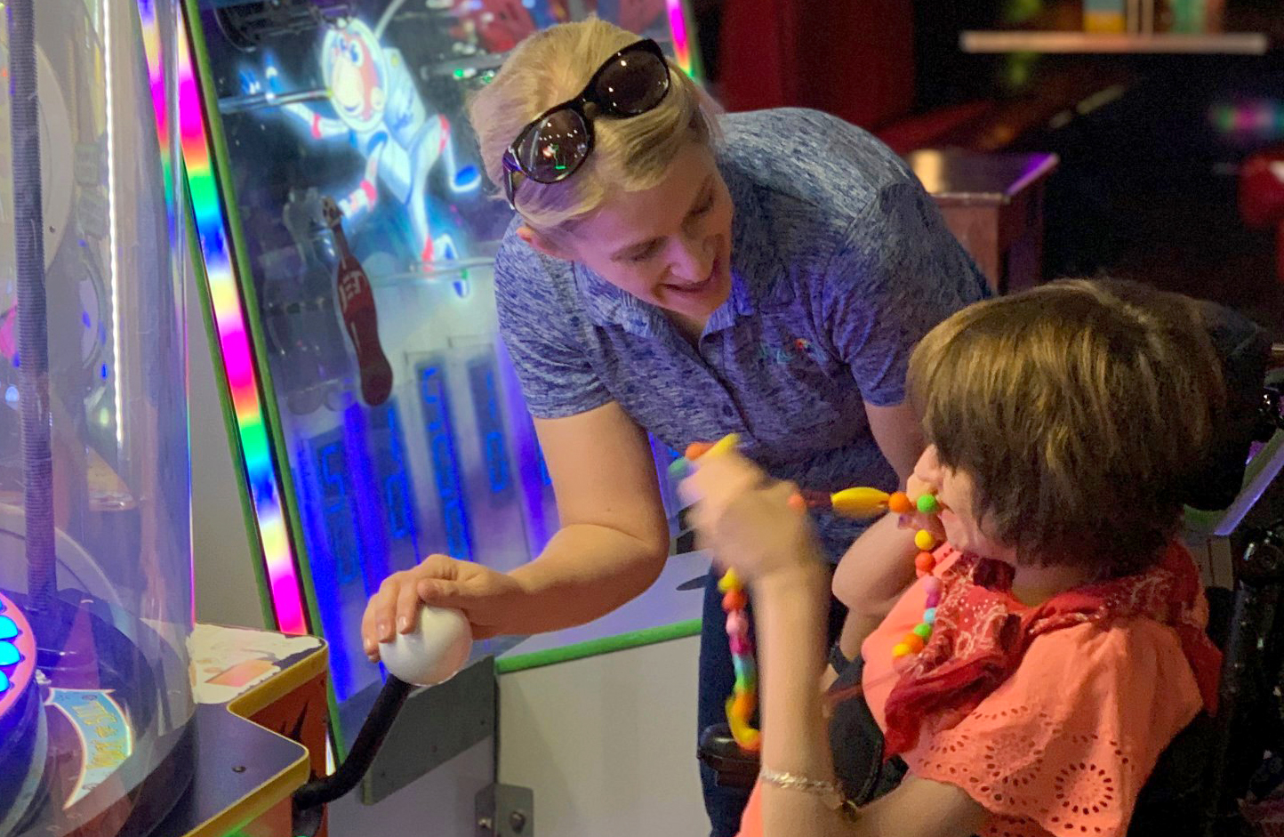 a woman and a child laughing while at an arcade