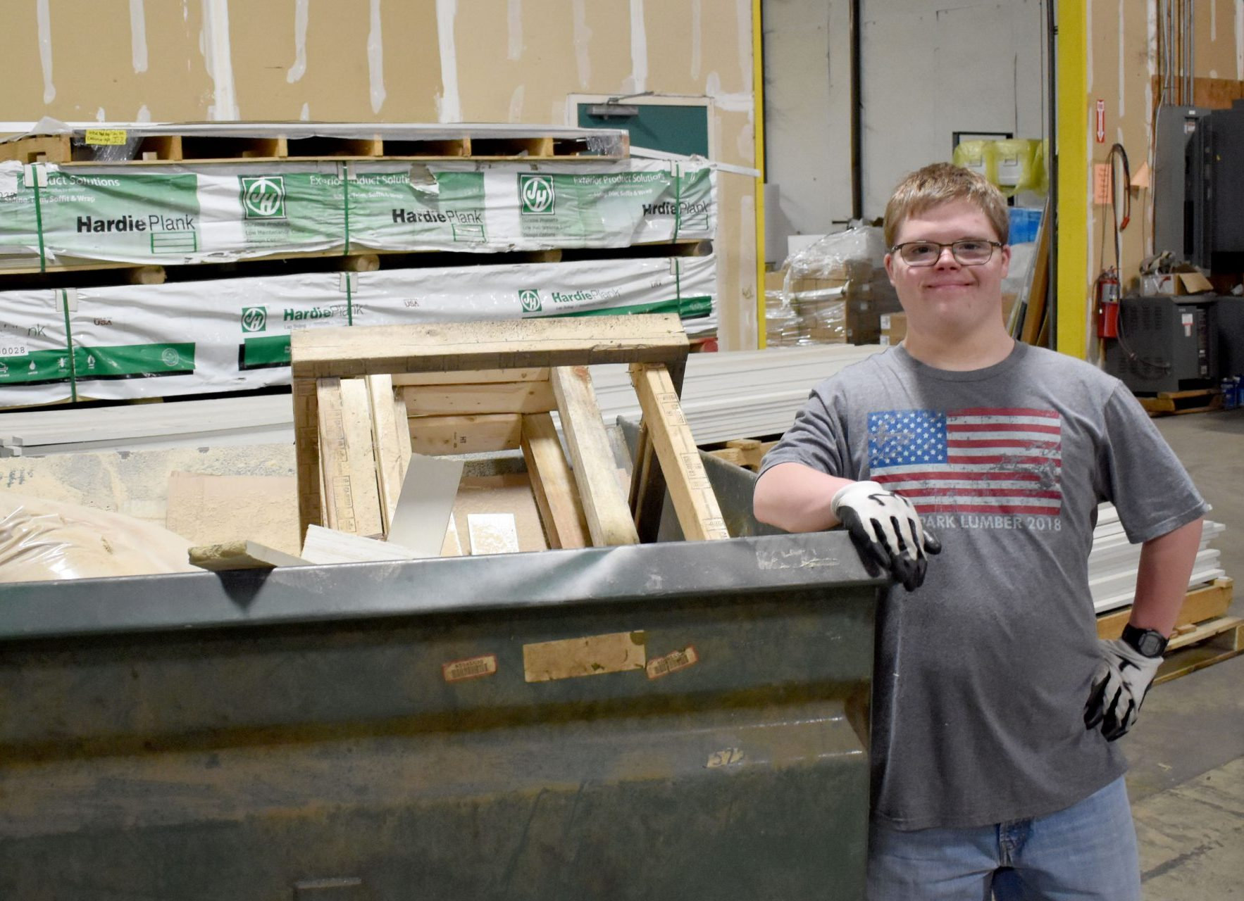 a man poses for a photo in a warehouse