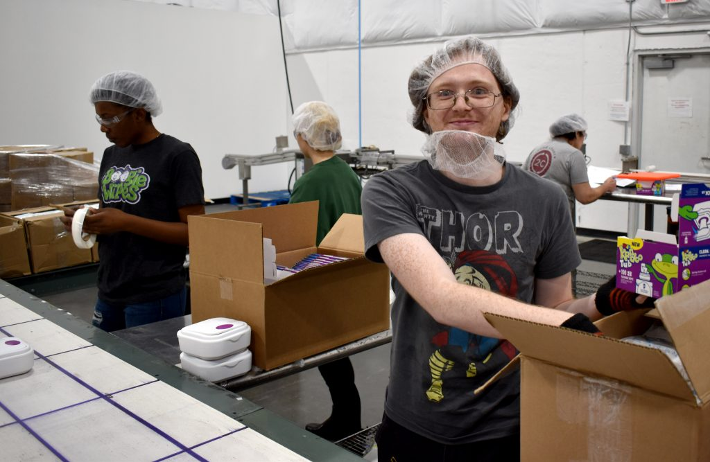 A man wearing a hair net smiles and fills boxes in a warehouse with other workers