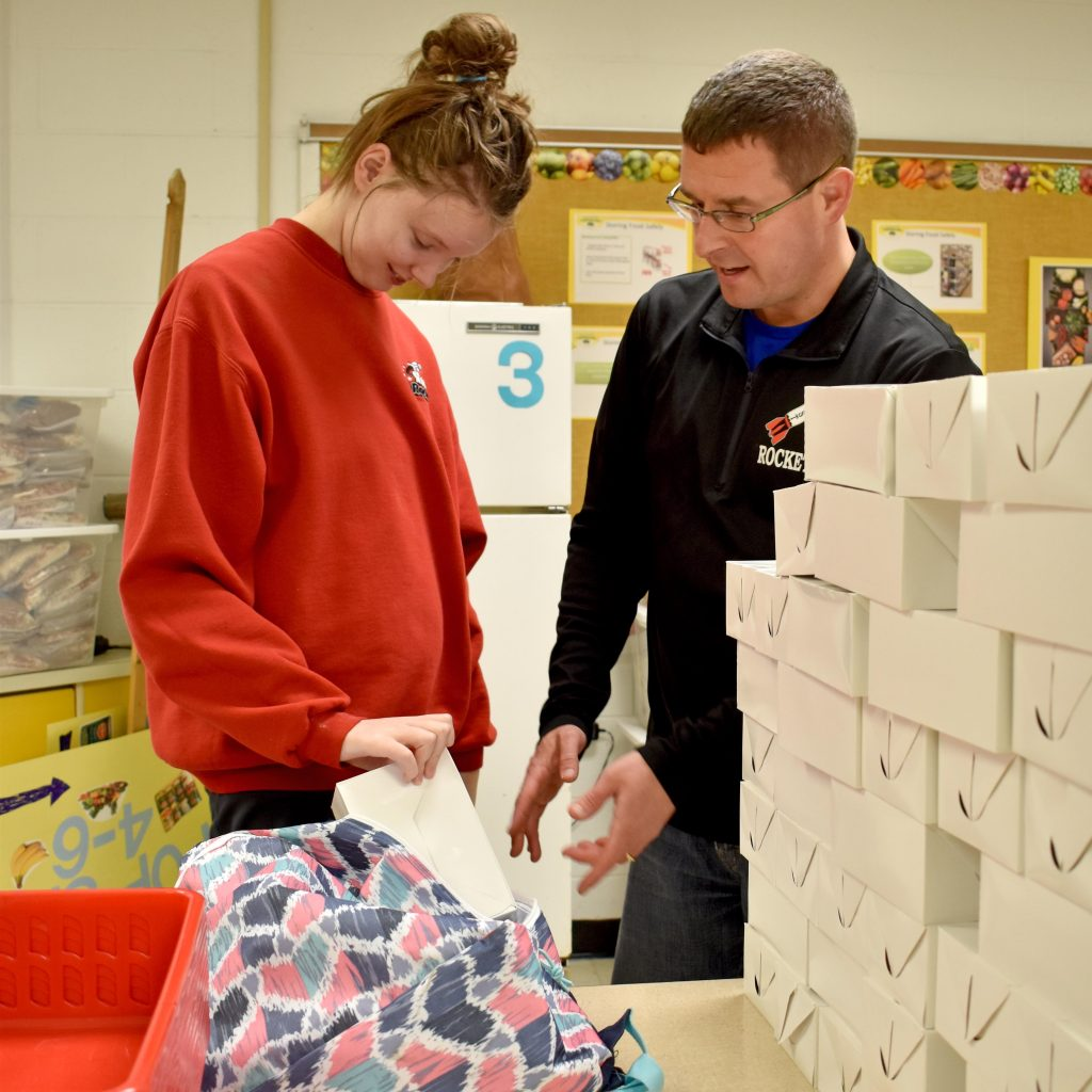 a male teacher and a female student stack boxes of food