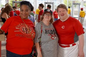 two women and a man wearing Cincinnati reds shirts smiling at a Reds game