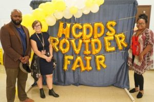 a man and two women smile next to baloons that spell HCDDS Provider Fair