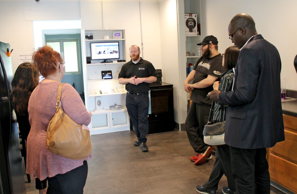 several people standing in a kitchen with smart displays in the background