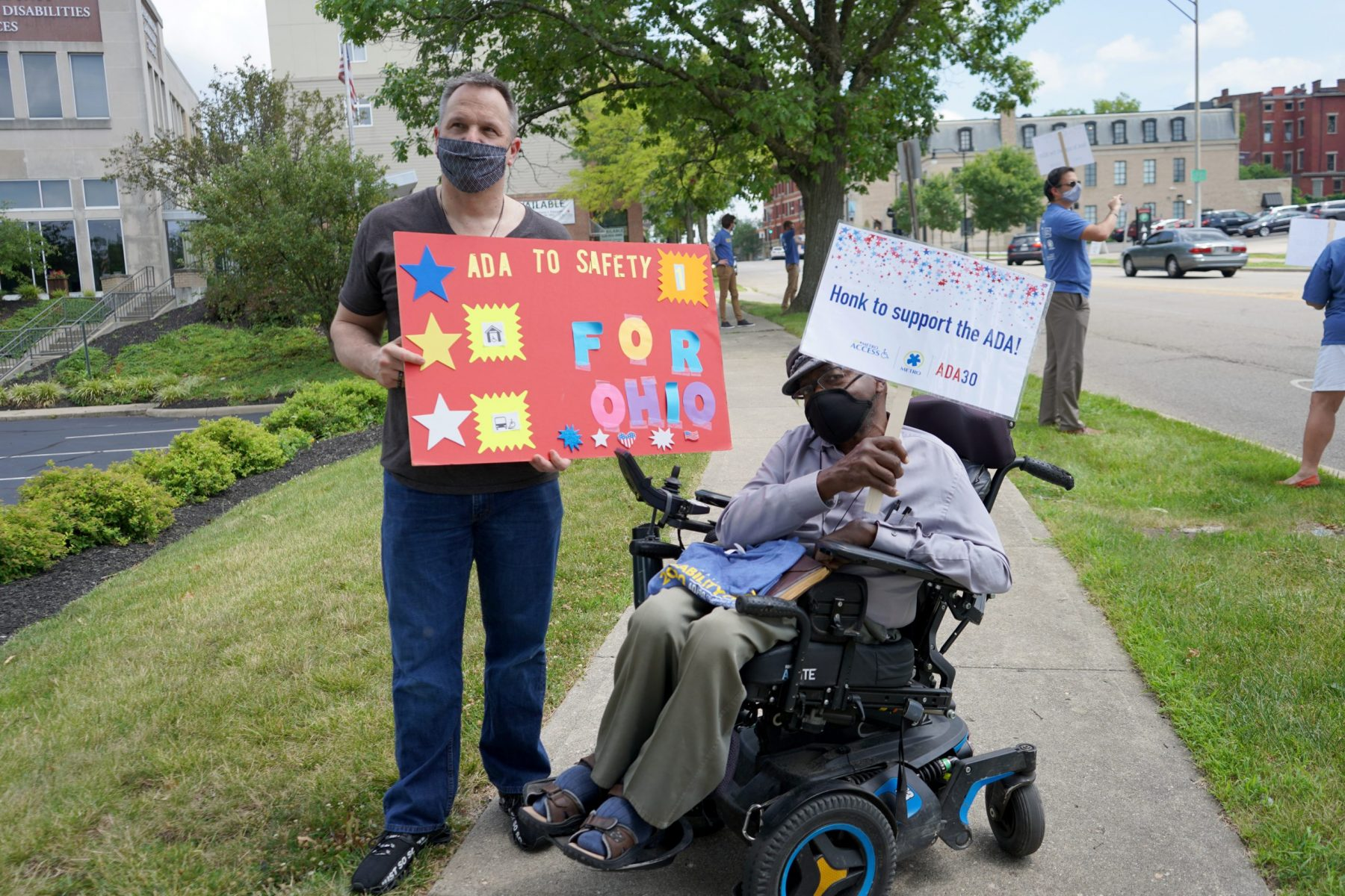 Two people holding signs to celebrate the ADA wave to passing cars outside the HCDDS office