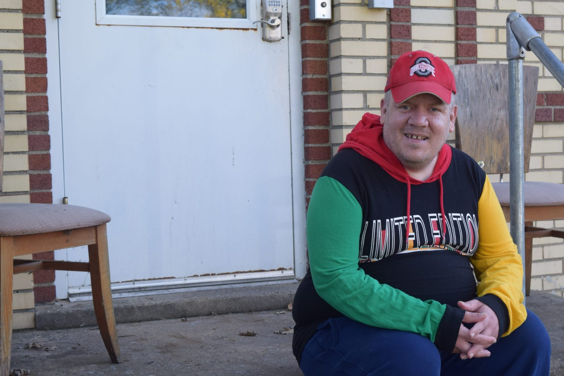 a man smiles while sitting on the front step of an apartment building