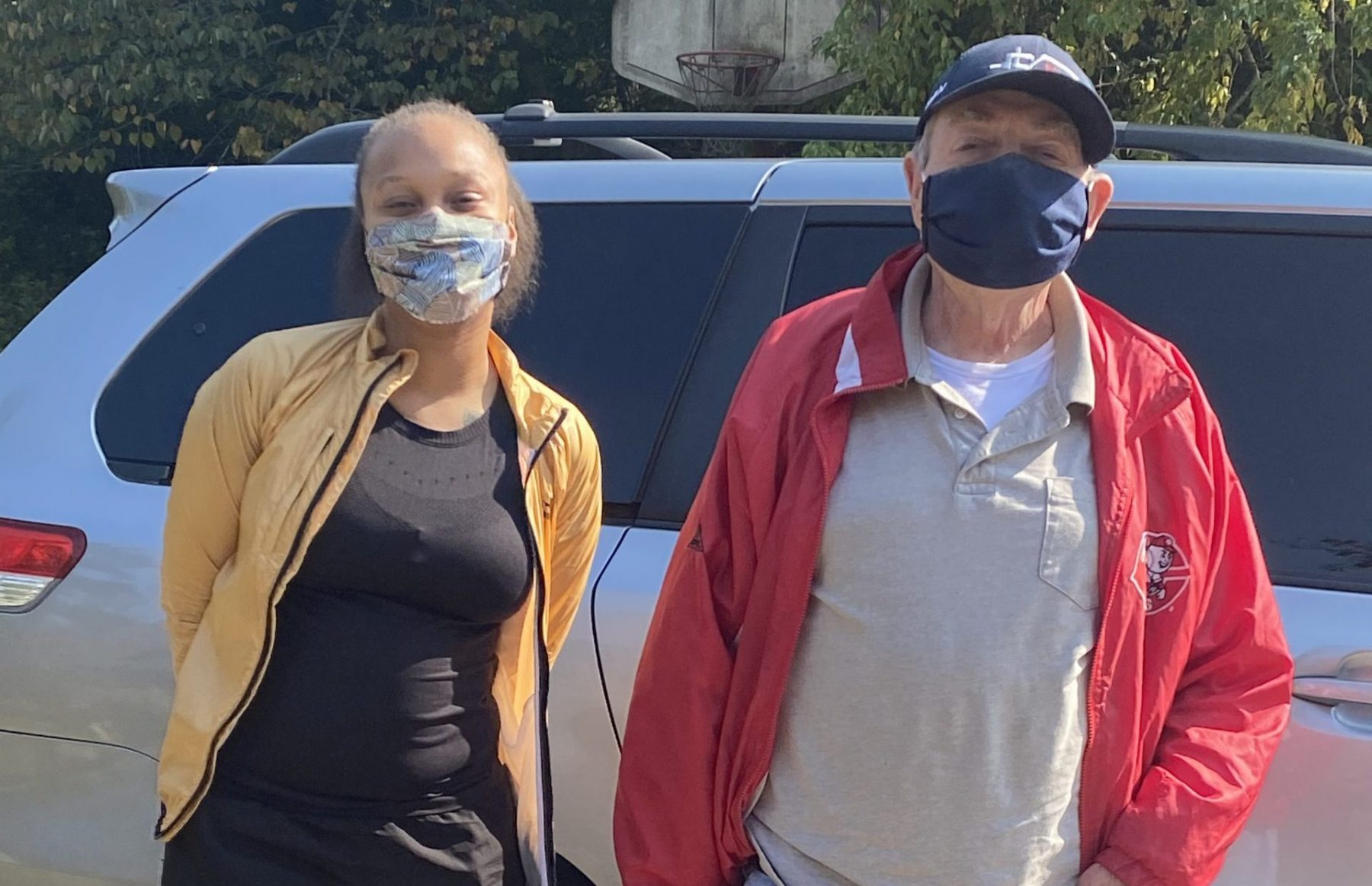a man and woman wearing masks and standing next to a car