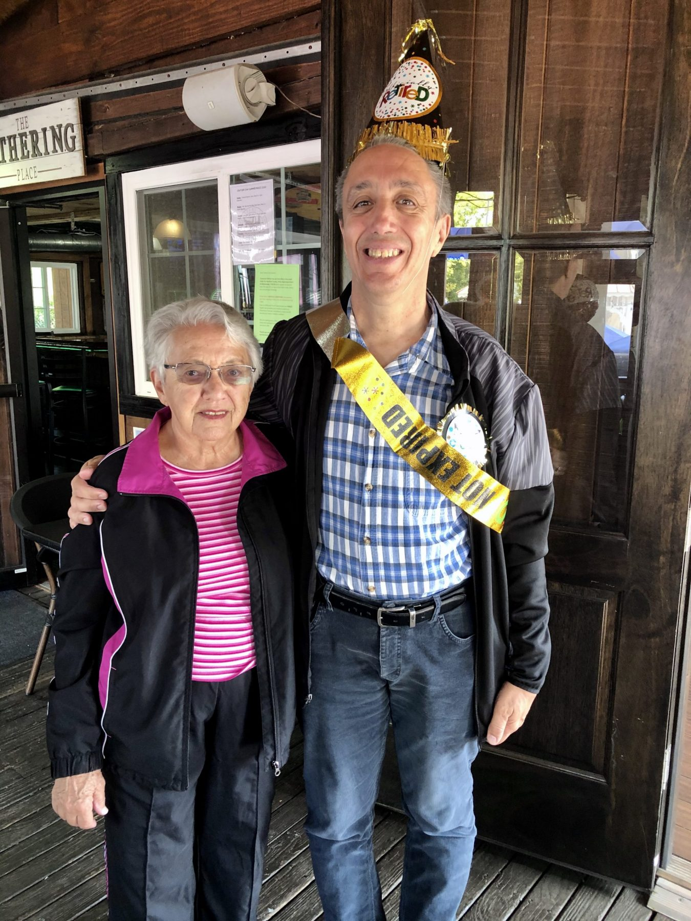 """A man wearing a party hat and sash that read """"retired"""" smiles with his arm over the shoulder of a woman"""