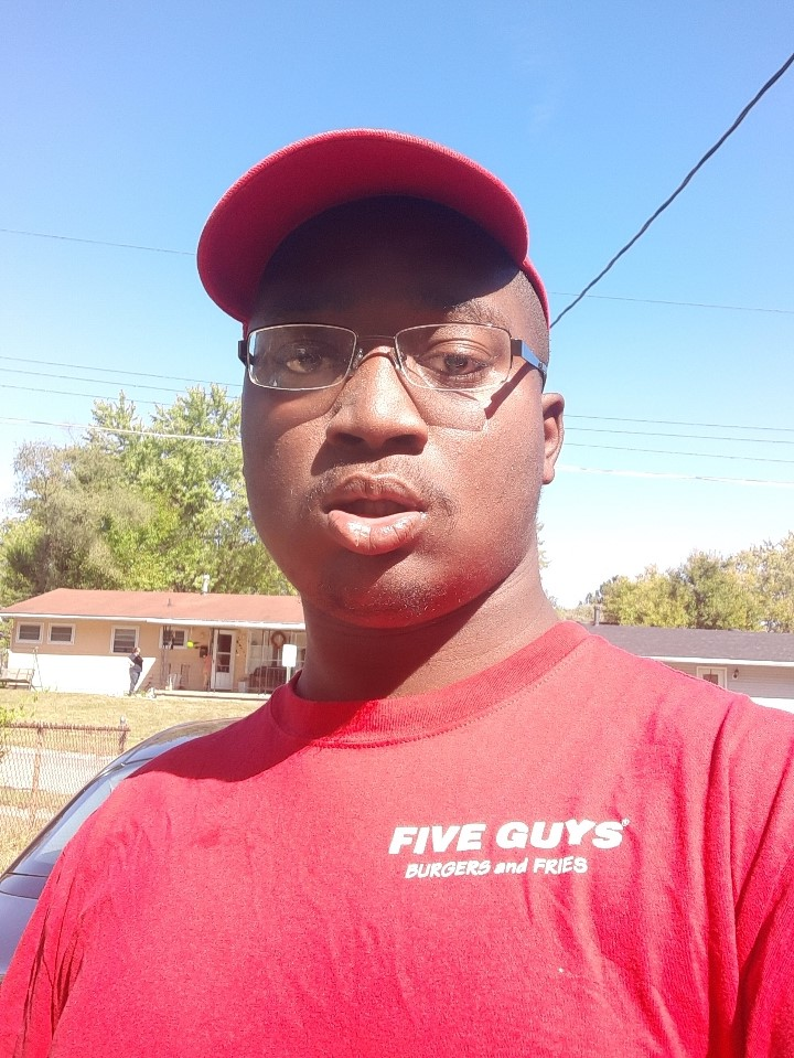 """A young man with glasses wearing a red hat and a red shirt reading """"five guys burgers and fries"""""""