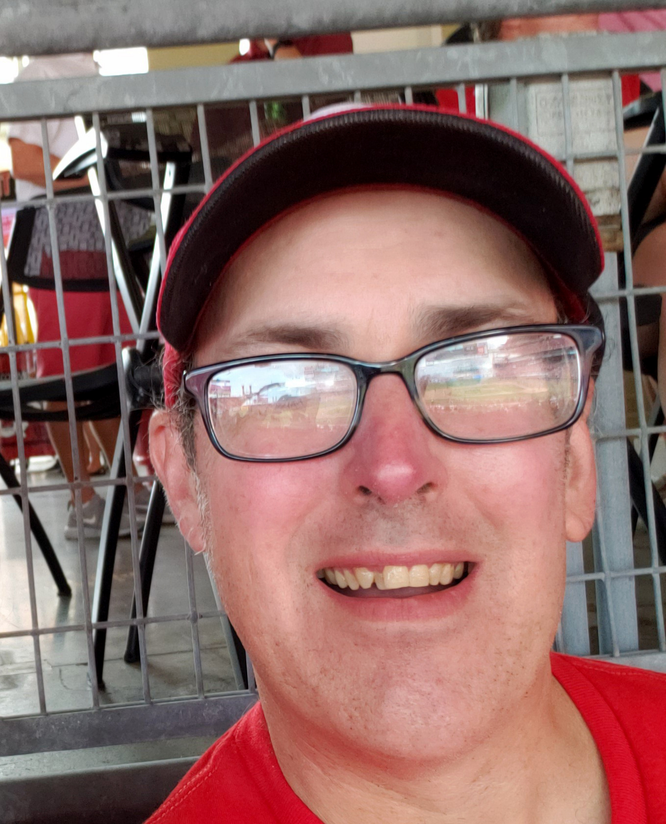 A man with glasses, a red hat, and a red shirt smiles