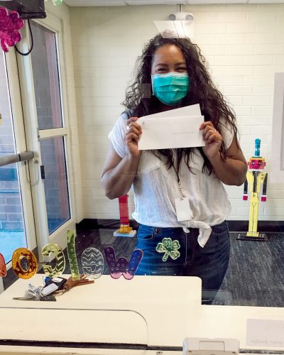 a woman wearing a mask shows envelopes to the camera